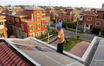 An Indian worker cleans solar panels fitted onto the roof of a residential house in Rabirashmi Abasan, a solar housing complex at Rajarhat close to Kolkata, on April 20, 2010. Consisting of 25 houses and a community hall,  the complex is India's first solar housing project with each home's tiles designed to generate 2 kW of power a day, primarily for direct domestic use but feeding surplus production into the electricity grid. April 22 marks the 40th Earth Day, which urges local action and increased awareness to understand and respect the environment. India, with its 1,2 billion citizens, faces challenges from rapid urbanisation and industrialisation, such as pollution, sanitation and water supply, as well as degradation of forests and agricultural lands, and is already the world's fifth largest carbon emitter despite a low per capita share. AFP PHOTO/Deshakalyan CHOWDHURY (Photo credit should read DESHAKALYAN CHOWDHURY/AFP via Getty Images)