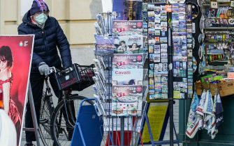 Un uomo con la mascherina in bicicletta davanti ad una edicola di piazza Castello, Torino, 28 febbraio 2020. ANSA/ TINO ROMANO