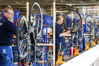 Workers assemble cycles on a production line at a Gazelle manufacturing facility in Dieren, some 120kms south-east of Amsterdam on April 14, 2020, which has restarted production after the factory was closed for three weeks due to the corona crisis. - The company has taken measures to protect its employees, such as installing plexiglass walls and creating workplaces in accordance with the 1.5 meter directive. (Photo by Piroschka VAN DE WOUW / ANP / AFP) / Netherlands OUT (Photo by PIROSCHKA VAN DE WOUW/ANP/AFP via Getty Images)