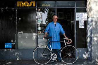 Italian bicycle maker Alberto Masi poses with one of his handmade bike in front of his workshop in Vigorelli Velodrome, on April 26, 2018 in Milan. - Alberto Masi is the son of Faliero Masi, one of the most famous frames builder for the greats riders as Fausto Coppi, Fiorenzo Magni, Louison Bobet, Jacques Anquetil, Felice Gimondi and Eddy Merckx. His workshop produces handmade bikes for his customers all over the world. (Photo by MARCO BERTORELLO / AFP)        (Photo credit should read MARCO BERTORELLO/AFP via Getty Images)
