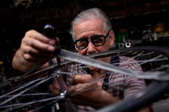 Mechanic and cycling passionate Raffaello Bianco works on a wheel in his mechanical workshop in the cellar of his apartment on July 7, 2020, in Turin. - Raffaello Bianco is an amateur bicycle mechanic repairing bicycle in a tiny garage near his home. Throughout his life he has mainly worked as a farrier, but he says the bicycle has always remained a greater passion. In 1985 he decided to set-up a small garage near his home in Turin and slowly built it up, making all the tools by himself. Among many amateur cyclists who are asking him to fix their bikes there are professional riders such as Fabio Fellini, of the Astana cycling team, and cycling legends of the 50s and 60s. (Photo by MARCO BERTORELLO / AFP) (Photo by MARCO BERTORELLO/AFP via Getty Images)