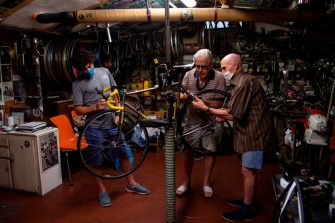 Mechanic and cycling passionate Raffaello Bianco (C) works in his mechanical workshop in the cellar of his apartment on July 7, 2020, in Turin. - Raffaello Bianco is an amateur bicycle mechanic repairing bicycle in a tiny garage near his home. Throughout his life he has mainly worked as a farrier, but he says the bicycle has always remained a greater passion. In 1985 he decided to set-up a small garage near his home in Turin and slowly built it up, making all the tools by himself. Among many amateur cyclists who are asking him to fix their bikes there are professional riders such as Fabio Fellini, of the Astana cycling team, and cycling legends of the 50s and 60s. (Photo by MARCO BERTORELLO / AFP) (Photo by MARCO BERTORELLO/AFP via Getty Images)