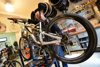 A mechanic repairs a bicycle in a workshop in Milan on May 21, 2013.  AFP PHOTO / GIUSEPPE CACACE        (Photo credit should read GIUSEPPE CACACE/AFP via Getty Images)