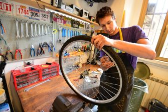 A mechanic repairs a tyre in a bicycle workshop in Milan on May 21, 2013.  AFP PHOTO / GIUSEPPE CACACE        (Photo credit should read GIUSEPPE CACACE/AFP via Getty Images)