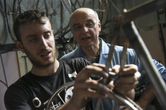 Italian bicycle maker Alberto Masi (R) looks at his employee, Italian frame maker Simone D'Urbino working in Masi's workshop in Vigorelli Velodrome, on April 26, 2018 in Milan. - Alberto Masi is the son of Faliero Masi, one of the most famous frames builder for the greats riders as Fausto Coppi, Fiorenzo Magni, Louison Bobet, Jacques Anquetil, Felice Gimondi and Eddy Merckx. His workshop produces handmade bikes for his customers all over the world. (Photo by MARCO BERTORELLO / AFP)        (Photo credit should read MARCO BERTORELLO/AFP via Getty Images)