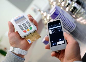 """An itinerant merchant uses the new Caisse d'Epargne """"Dilizi"""" billing system, that allows credit card payments thanks to a credit card reader and a smartphone, on May 27, 2014 in Lille, northern France. AFP PHOTO / FRANCOIS LO PRESTI / AFP PHOTO / FRANCOIS LO PRESTI        (Photo credit should read FRANCOIS LO PRESTI/AFP via Getty Images)"""