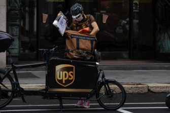 MILAN, ITALY - SEPTEMBER 23: A delivery man for United Parcel Service (UPS) handles a parcel next to his cargo bike on September 23, 2020 in Milan, Italy. Since the end of lockdown Milan authorities have added a further 35 kilometers of pop-up bike lanes and cycle paths and encouraged cycling and riding e-scooters as a safer form of transport away from jam-packed buses or subway trains, in order to promote social distancing in response to COVID-19. (Photo by Emanuele Cremaschi/Getty Images)