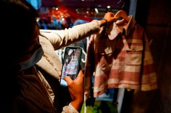 """A woman uses her phone to scan a shirt inside the AliExpress pop-up store in Paris on September 24, 2020. - The global marketplace of Chinese e-commerce giant Alibaba, AliExpress, opened from September 24 to 26 a pop-up store in Paris for the first time in France, aiming to showcase its fashion and decoration products and its concept of """"shoppertainment"""" in video streams. (Photo by GEOFFROY VAN DER HASSELT / AFP) (Photo by GEOFFROY VAN DER HASSELT/AFP via Getty Images)"""
