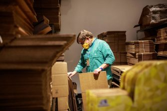 """Legacy Toys Store Manager Jeff Kasper sorts through shipping boxes at the store in the Mall of America on June 16, 2020 in Bloomington, Minnesota. - The US economy continues to bleed fresh jobs in the aftermath of COVID-19 shutdowns, even as it reopens and as the Paycheck Protection Program (PPP) and other federal initiatives mitigate some of the downturn's harshest impacts. Legacy Toys has used its PPP loan to build out an e-commerce business from its seven stores in Minnesota and North Dakota that now see """"skyrocketing"""" demand for curbside pickup from reopened stores, said owner Brad Ruoho. But Legacy, which obtained a $160,000 PPP loan, still has only rehired 35 of 75 staff members. The malls are operating at reduced hours, which means the stores require fewer workers, Ruoho said. (Photo by Kerem Yucel / AFP) (Photo by KEREM YUCEL/AFP via Getty Images)"""