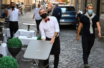 A waiter wearing a face mask sets up tables outside a restaurant in downtown Rome on September 25, 2020 during the COVID-19 pandemic, caused by the novel coronavirus. - Italy, which was hit hard by the first wave of the coronavirus, is today an exception in Europe with a limited number of new cases, a result obtained at the price of strict anti-COVID measures, hailed on September 25, 2020 by the World Health Organization (WHO). (Photo by Vincenzo PINTO / AFP) (Photo by VINCENZO PINTO/AFP via Getty Images)