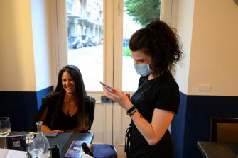 VINOVO, ITALY - JUNE 04: A waitress with protective mask at work during the reopening to the customers of a restaurant on June 04, 2020 in Vinovo, Italy. Many Italian businesses have been allowed to reopen, after more than two months of a nationwide lockdown meant to curb the spread of Covid-19. (Photo by Diego Puletto/Getty Images)