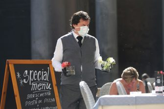 ROME, ITALY - MARCH 11: A waiter wearing protective mask sets a table  at the Pantheon Square on March 11, 2020 in Rome, Italy. The Italian Government has taken the unprecedented measure of a nationwide lockdown in an effort to fight the world's second-most deadly coronavirus outbreak outside of China. The movements in and out are allowed only for work and health reasons proven by a medical certificate. The justifications for the movements needs to be certified with a self-declaration by filling in forms provided by the police forces in charge of the checks. (Photo by Franco Origlia/Getty Images)