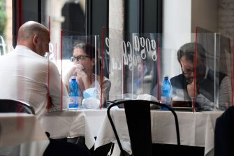 People have lunch at tables partitioned with plexiglas at the Goga Cafe on May 18, 2020 in central Milan during the country's lockdown aimed at curbing the spread of the COVID-19 infection, caused by the novel coronavirus. - Restaurants and churches reopen in Italy on May 18, 2020 as part of a fresh wave of lockdown easing in Europe and the country's latest step in a cautious, gradual return to normality, allowing businesses and churches to reopen after a two-month lockdown. (Photo by Miguel MEDINA / AFP) (Photo by MIGUEL MEDINA/AFP via Getty Images)