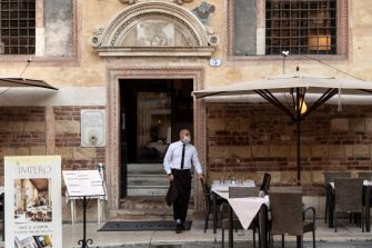 A waiter wearing a protective face mask stands outside a restaurant in Piazza dei Signori on July 25, 2020 in Verona, northern Italy. (Photo by MARCO BERTORELLO / AFP) (Photo by MARCO BERTORELLO/AFP via Getty Images)