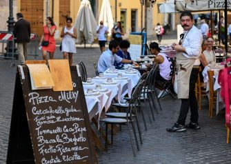A waiter looks on at a restaurant's terrace in Rome's Jewish Quarter on September 15, 2020 during the COVID-19 infection, caused by the novel coronavirus. (Photo by Vincenzo PINTO / AFP) (Photo by VINCENZO PINTO/AFP via Getty Images)