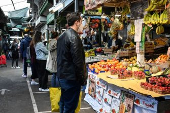 A customer wearing protective facemask and gloves waits to be serves at a fruit and vegetable of the local market in the district of Trionfale, in Rome, on April 16, 2020, during a strict lockdown of the country, aimed at curbing the spread of the COVID-19 epidemic caused by the novel coronavirus. (Photo by Andreas SOLARO / AFP) (Photo by ANDREAS SOLARO/AFP via Getty Images)