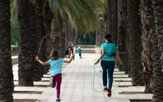 TOPSHOT - A woman jumps rope with a girl in Valencia on April 26, 2020, amid a national lockdown to prevent the spread of the COVID-19 disease. - After six weeks stuck at home, Spain's children were being allowed out today to run, play or go for a walk as the government eased one of the world's toughest coronavirus lockdowns. Spain is one of the hardest hit countries, with a death toll running a more than 23,000 to put it behind only the United States and Italy despite stringent restrictions imposed from March 14, including keeping all children indoors. Today, with their scooters, tricycles or in prams, the children accompanied by their parents came out onto largely deserted streets. (Photo by JOSE JORDAN / AFP) (Photo by JOSE JORDAN/AFP via Getty Images)