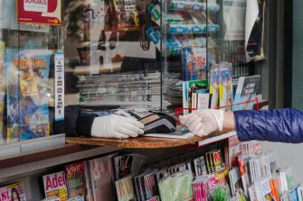 SEVILLE, SPAIN - MARCH 29: A woman wearing latex gloves pays the newspaper with her credit card in a kiosk on March 29, 2020 in Seville, Spain. Spain will forbid all non-essential economic activity until April 9 as Coronavirus quarantine measures continue. The Coronavirus (COVID-19) pandemic has spread to many countries across the world, claiming over 30,000 lives and infecting hundreds of thousands more. (Photo by Niccolo Guasti/Getty Images)