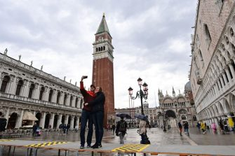 """A general view shows a couple standing on an elevated walkway, taking a selfie photo with their smartphone at St. Mark's square in Venice on October 3, 2020 as a high tide """"Alta Acqua"""" phenomenon was expected, following a peak of water following bad weather and potential intense sirocco winds along the entire Adriatic basin. - The rise in water levels, expected to peak at midday on October 3, 2020, was limited by a new system of mobile gates. The MOSE project (Moses in Italian, Electromagnetic Experimental Module) is a complex engineering system allowing the """"waterproofing"""" of Venice through 78 dikes placed at the lagoon's entry points. (Photo by MIGUEL MEDINA / AFP) (Photo by MIGUEL MEDINA/AFP via Getty Images)"""