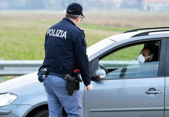An Italian National Police officer talks to a person in a car, wearing a respiratory mask, at the entrance of the small town of Casalpusterlengo, southeast of Milan, on February 23, 2020, under the shadow of a new coronavirus outbreak, as Italy took drastic containment steps as worldwide fears over the epidemic spiralled. (Photo by Miguel MEDINA / AFP) (Photo by MIGUEL MEDINA/AFP via Getty Images)