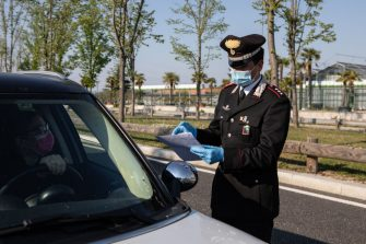 MILAN, ITALY - APRIL 10: An Italian Carabinieri Captain, wearing a respiratory mask, checks the documents of a woman at a road block on April 10, 2020 in Milan, Italy. The Italian Government has further strengthened police controls nationwide, in the effort to prevent people leaving the quarantine as the long Easter weekend begins. There have been well over 140,000 reported COVID-19 cases in Italy and more than 18,000 related deaths, but the officials are confident the peak of new cases has passed. (Photo by Emanuele Cremaschi/Getty Images)