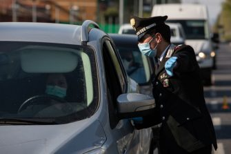 MILAN, ITALY - APRIL 10: An Italian Carabinieri officer, wearing a respiratory mask, talks to a woman at a road block on April 10, 2020 in Milan, Italy. The Italian Government has further strengthened police controls nationwide, in the effort to prevent people leaving the quarantine as the long Easter weekend begins. There have been well over 140,000 reported COVID-19 cases in Italy and more than 18,000 related deaths, but the officials are confident the peak of new cases has passed. (Photo by Emanuele Cremaschi/Getty Images)
