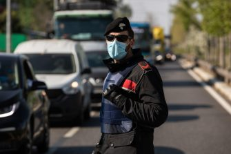MILAN, ITALY - APRIL 10: An Italian Carabinieri officer, wearing a respiratory mask, stands guard at a road block on April 10, 2020 in Milan, Italy. The Italian Government has further strengthened police controls nationwide, in the effort to prevent people leaving the quarantine as the long Easter weekend begins. There have been well over 140,000 reported COVID-19 cases in Italy and more than 18,000 related deaths, but the officials are confident the peak of new cases has passed. (Photo by Emanuele Cremaschi/Getty Images)