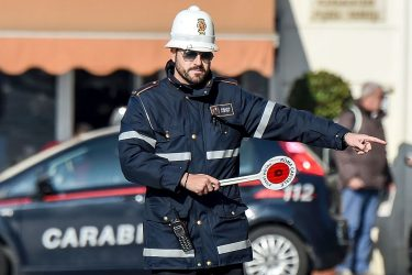 A police officer controls cars and scooters during the limited traffic day, in centeral Rome, on December 29, 2015.  A second day with limited traffic of odd and even car plate numbers was enforced in the hope of lowering air pollution. A lack of rainfall has led pollution levels to climb in recent weeks, and has prompted the administration of Rome, to appeal to drivers to respect the rules.    / AFP / ANDREAS SOLARO        (Photo credit should read ANDREAS SOLARO/AFP via Getty Images)