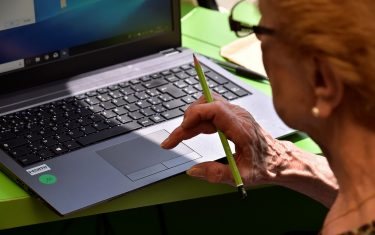 """An elderly woman reads on a screen during a computer workshop in the """"digital bus (""""bus numerique"""") in Villandraut, near Sauternes, southwestern France, on May 22, 2018. - The """"digital bus (""""bus numerique"""") has been launched by the CARSAT (French Pension insitution - Caisse d'assurance retraite et de la sante au travail) of Aquitaine region at the end of 2016 to promote computer and internet access for elderly people. (Photo by GEORGES GOBET / AFP)        (Photo credit should read GEORGES GOBET/AFP via Getty Images)"""