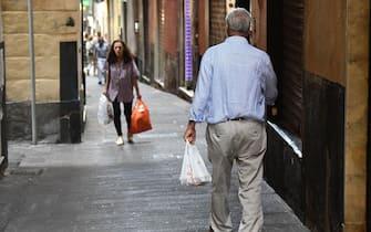 Anziani con le borse della spesa, in giro per la citta'. Genova, 01 agosto 2019. ANSA/LUCA ZENNARO