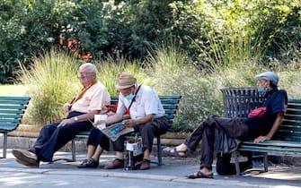 Un gruppo di signori anziani si riposa all'ombra in questa giornata di caldo intenso in Piazza Castello a Milano, 31 luglio 2020.ANSA/Mourad Balti Touati