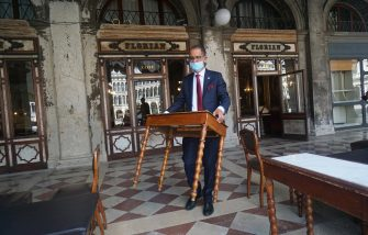 The director of the historic Caffè Florian, Renato Costantini, while placing a table outside in San Marco square in Venice, Italy, 12 June 2020. ANSA / ANDREA MEROLA