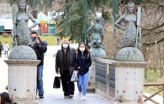Due persone che indossano maschrine sanitarie, passeggiano nei vicinanze del Castello sforzesco, Milano, 26 febbraio 2020.In pochissimi giorni l'emergenza coronavirus sta mettendo in crisi il settore del turismo che stasubendo un calo di oltre il 40%. ANSA/PAOLO SAILMORAGO
