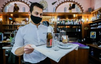 A waiter wears a protective face mask in a restaurant, in Turin, northern Italy, 16 October 2020. Retail commercial activities will stop from midnight to five a.m. in Piedmont starting 18 October, according to a new ordinance signed by Governor Alberto Cirio Friday to combat the resurgence of the Covid-19 pandemic. Pharmacies will be excluded, the ordinance said. ANSA/TINO ROMANO
