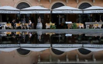 Un ristorante semi-deserto (riflesso in una pozzanghera) all'ora di pranzo a piazza Navona, Roma, 27 ottobre 2020. ANSA/ALESSANDRO DI MEO