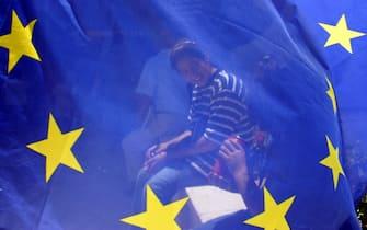 A Palestinian girl sits behind a European Union flag in the AL-Bireh municipality, Ramallah, Thursday 26 June 2003. ANSA/ATEF SAFADI