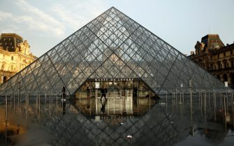 epa08262869 Visitors pass by the pyramid of the Louvre Museum in Paris, France, 01 March 2020. Louvre museum has closed its door to visitors today. The famous museum held a staff meeting about the coronavirus outbreak. Media reports, the museum's employees and guards feared to be contaminated by visitors's flow over  coronavirus epidemic COVID-19 disease.  EPA/YOAN VALAT