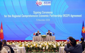 epa08821143 Vietnam's Prime Minister Nguyen Xuan Phuc (L) and Minister of Industry and Trade Tran Tuan Anh (R) during the virtual signing ceremony for the Regional Comprehensive Economic Partnership (RCEP) in Hanoi, Vietnam, 15 November 2020. The virtual 37th ASEAN Summit and related summits take place from 12 to 15 November 2020 at the International Convention Center (ICC) in Hanoi.  EPA/LUONG THAI LINH