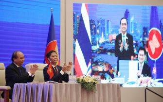 epa08821132 Vietnam's Prime Minister Nguyen Xuan Phuc (L) and Minister of Industry and Trade Tran Tuan Anh (R) during the virtual signing ceremony for the Regional Comprehensive Economic Partnership (RCEP) in Hanoi, Vietnam, 15 November 2020. The virtual 37th ASEAN Summit and related summits take place from 12 to 15 November 2020 at the International Convention Center (ICC) in Hanoi.  EPA/LUONG THAI LINH