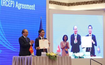 epa08821133 Vietnam's Prime Minister Nguyen Xuan Phuc (L) and Minister of Industry and Trade Tran Tuan Anh (2-L) hold the documents after the virtual signing ceremony for the Regional Comprehensive Economic Partnership (RCEP) in Hanoi, Vietnam, 15 November 2020. The virtual 37th ASEAN Summit and related summits take place from 12 to 15 November 2020 at the International Convention Center (ICC) in Hanoi.  EPA/LUONG THAI LINH