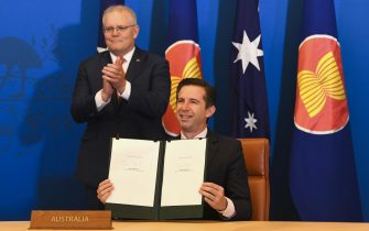 epa08821127 Australian Trade Minister Simon Birmingham (R) and Australian Prime Minister Scott Morrison (L) react after signing the Regional Comprehensive Economic Partnership (RCEP) during a virtual signing ceremony at Parliament House in Canberra, Australia, 15 November 2020.  EPA/LUKAS COCH NAUSTRALIA AND NEW ZEALAND OUT