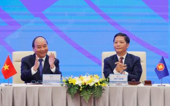 epa08821110 Vietnam's Prime Minister Nguyen Xuan Phuc (L) and Minister of Industry and Trade Tran Tuan Anh (R) during the signing ceremony for the Regional Comprehensive Economic Partnership (RCEP) in Hanoi, Vietnam, 15 November 2020. The virtual 37th ASEAN Summit and related summits take place from 12 to 15 November 2020 at the International Convention Center (ICC) in Hanoi.  EPA/MINH HOANG