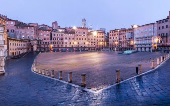 """Panorama view on the main square """"Il Campo"""" of the medieval town of Siena on twilight during the lockdown emergency period aimed at stopping the spread of the Covid-19 coronavirus. Although the lockdown and full absence of people, the scenery of the Italian squares and monuments remain fascinating, Siena, Italy, 23 April 2020(ANSA foto Fabio Muzzi)"""