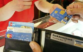 Un uomo paga con carta di credito in una foto d'archivio. ANSA / CIRO FUSCO