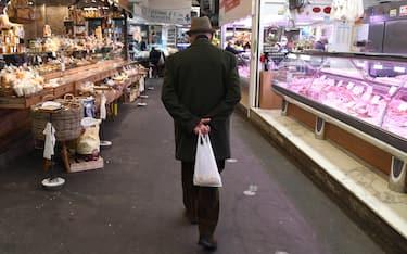Un cliente del Mercato Orientale effettua acquisti nel primo giorno di spesa con sconto per gli over 65 in Liguria. Coloro che effettuerannocompere in fasce orarie 'protette',  gli orarie sono 9-11 e 13 -16, avrannoo uno sconto che va dal 5% al 10% nei mercati e negozi  aderenti all'iniziativa voluta da regione Liguria, Camera di Commercio e Comuni, per incentivare gli anziani a uscire in momenti in cui i negozi sono meno affollati. ANSA/LUCA ZENNARO