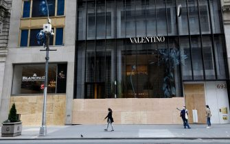 epa08461017 People walk past the Blancpain and Valentino store boarded up windows on Fifth Avenue after looting riots a night earlier as part of the response by protesters to George Floyd's death, in New York, New York, USA, 02 June 2020. A bystander's video posted online on 25 May, shows George Floyd pleading with arresting officers that he couldn't breathe as an officer knelt on his neck. The unarmed black man soon became unresponsive, and was later pronounced dead. According to reports on 29 May, Derek Chauvin, the police officer at the center of the incident, has been taken into custody and charged with murder in the death of George Floyd.  EPA/JASON SZENES