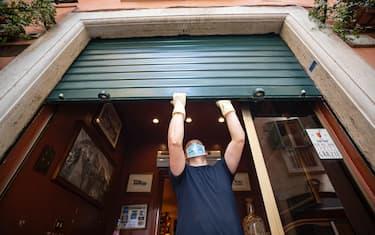 Un dipendente di un ristorante del centro storico di Roma alza la serranda durante l'emergenza Covid-19, Roma 17 maggio 2020. ANSA/MASSIMO PERCOSSI