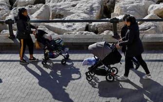 Mamme a passeggio sul lungomare con i propri figli