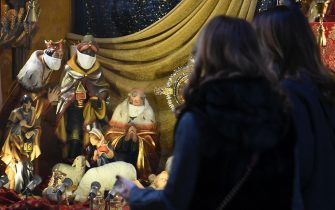 Due donne guardano la vetrina di un negozio di articoli religiosi che espone un presepe con i Re Magi che indossano la mascherina, Roma, 16 dicembre 2020.   MAURIZIO BRAMBATTI/ANSA