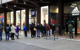 People wait in line outside a boutique in Corso Vittorio Emanuele as they go shopping during Christmas shopping season amid the second wave of the Covid-19 Coronavirus pandemic, in Milan, Italy, 05 December 2020. Italian government on 03 December passed a strict package of restrictions aimed at stopping the festive season fuelling a third wave of COVID-19 contagion. The package includes a ban on travelling between regions between 21 December and 6 January and a ban on moving outside one's home town on Christmas Day, St Stephen's Day and New Year's Day. The government has also maintained the current night curfew, with people not allowed out of their homes from 10pm until 5am, except for work or health reasons or other urgent situations. ANSA/ PAOLO SALMOIRAGO